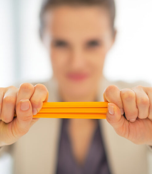 Closeup on business woman holding pencils stack